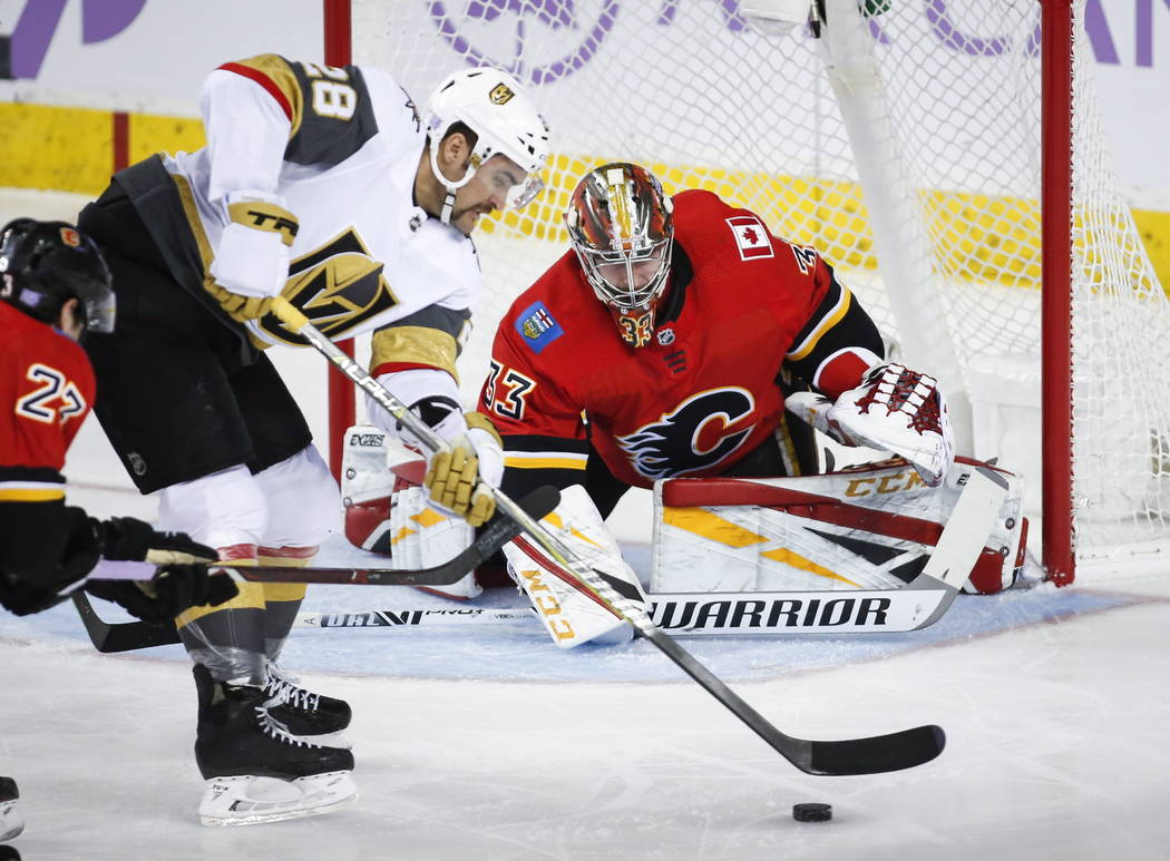 William Carrier de los Vegas Golden Knights, a la izquierda, intenta pasar el puck por el portero David Rittich de los Calgary Flames, de la República Checa, durante la primera acción de hockey ...