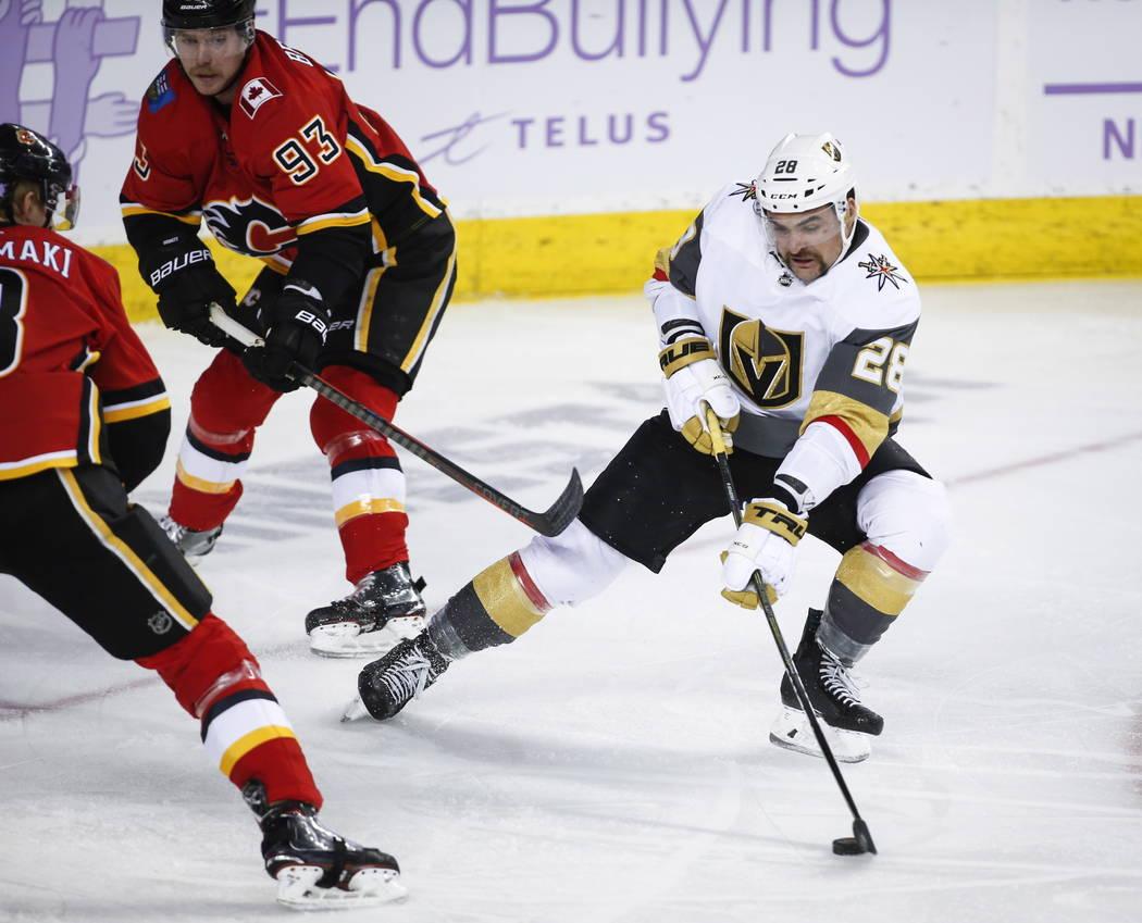 William Carrier, de los Golden Knights de Las Vegas, a la derecha, le dispara a Sam Bennett, centro, y Juuso Valimaki, de los Calgary Flames, durante el segundo tiempo del partido contra los Calga ...