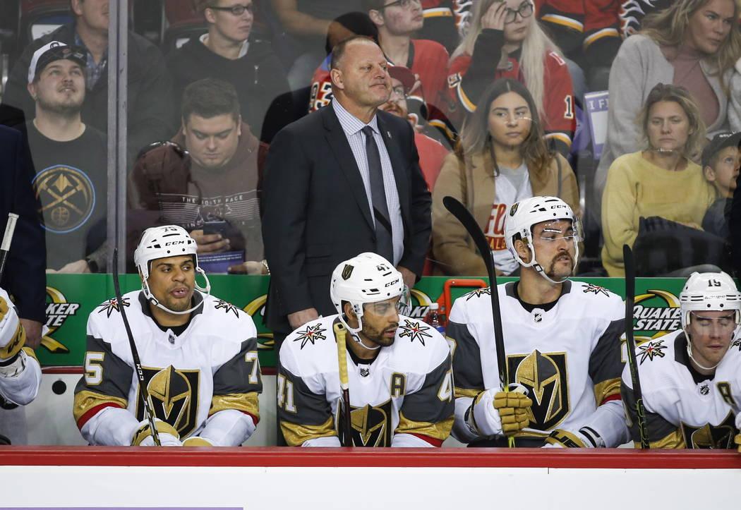 El entrenador en jefe de los Golden Knights de Las Vegas, Gerard Gallant, en el centro superior, observa la acción durante el segundo tiempo del juego de hockey de la NHL contra los Calgary Flame ...