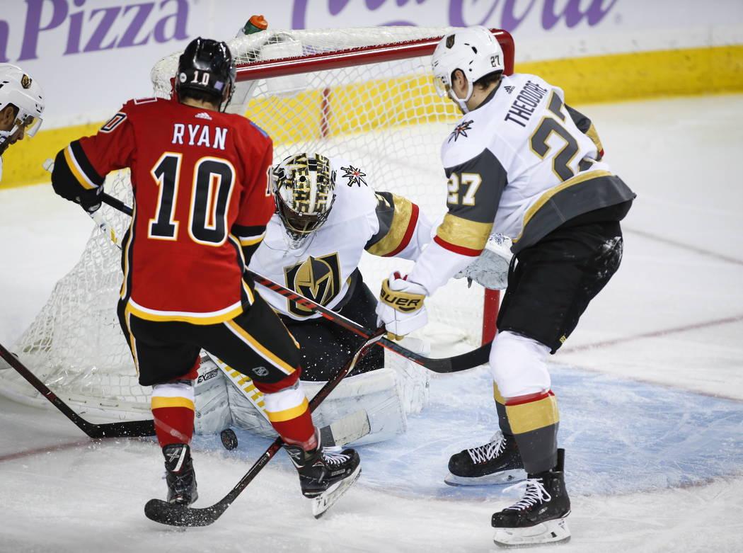 Malcolm Subban, portero de los Golden Knights de Las Vegas, detiene un disparo de Derek Ryan de los Calgary Flames, a la izquierda, mientras Shea Theodore de los Golden Knights observa durante el ...