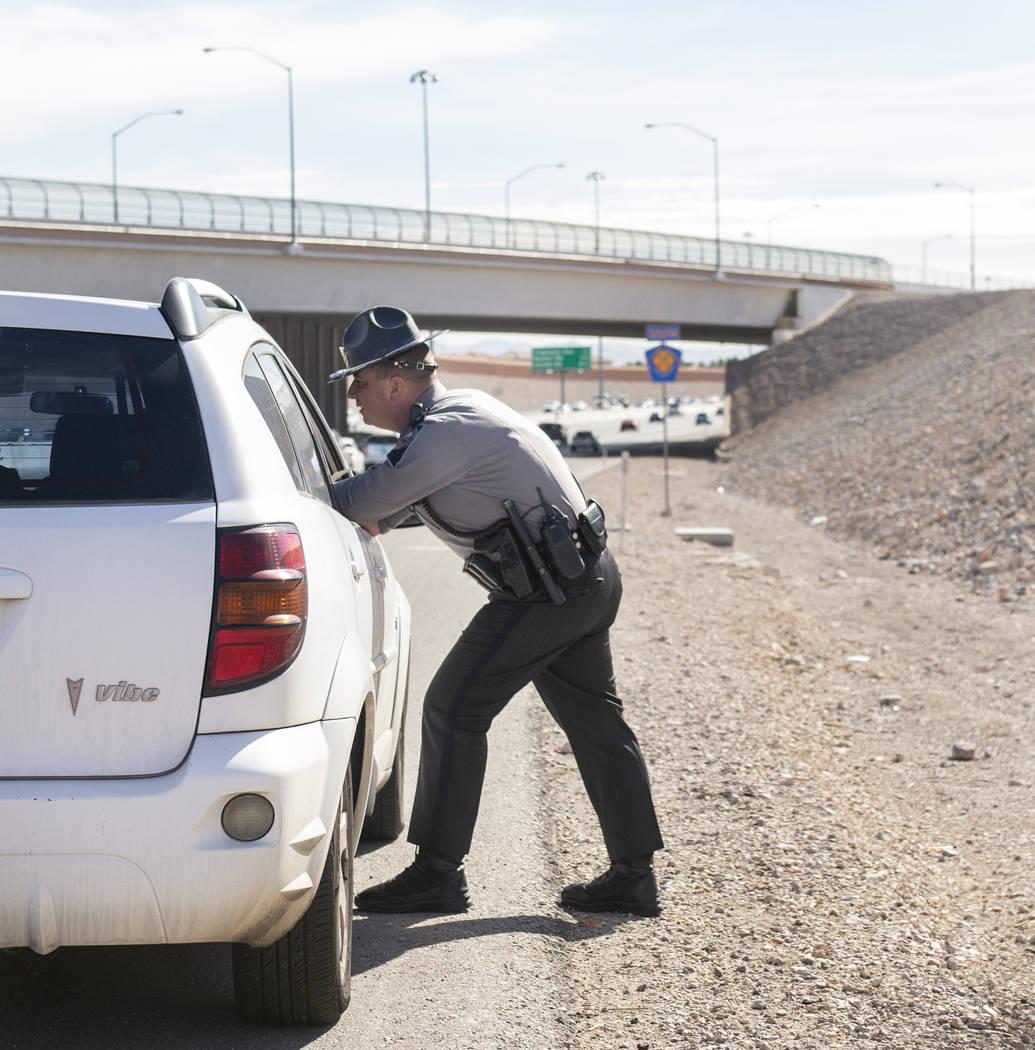 Jason Buratczuk, oficial de información y educación pública de la Patrulla de Carreteras de Nevada, habla con una conductora después de detenerla por exceso de velocidad en el 215 Beltway en L ...
