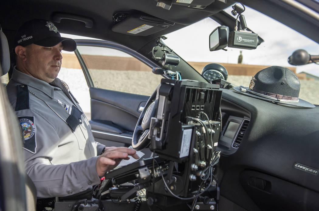 Jason Buratczuk, oficial de información y educación pública de la Patrulla de Carreteras de Nevada, archiva la información en una computadora después de detener a un conductor por exceso de v ...
