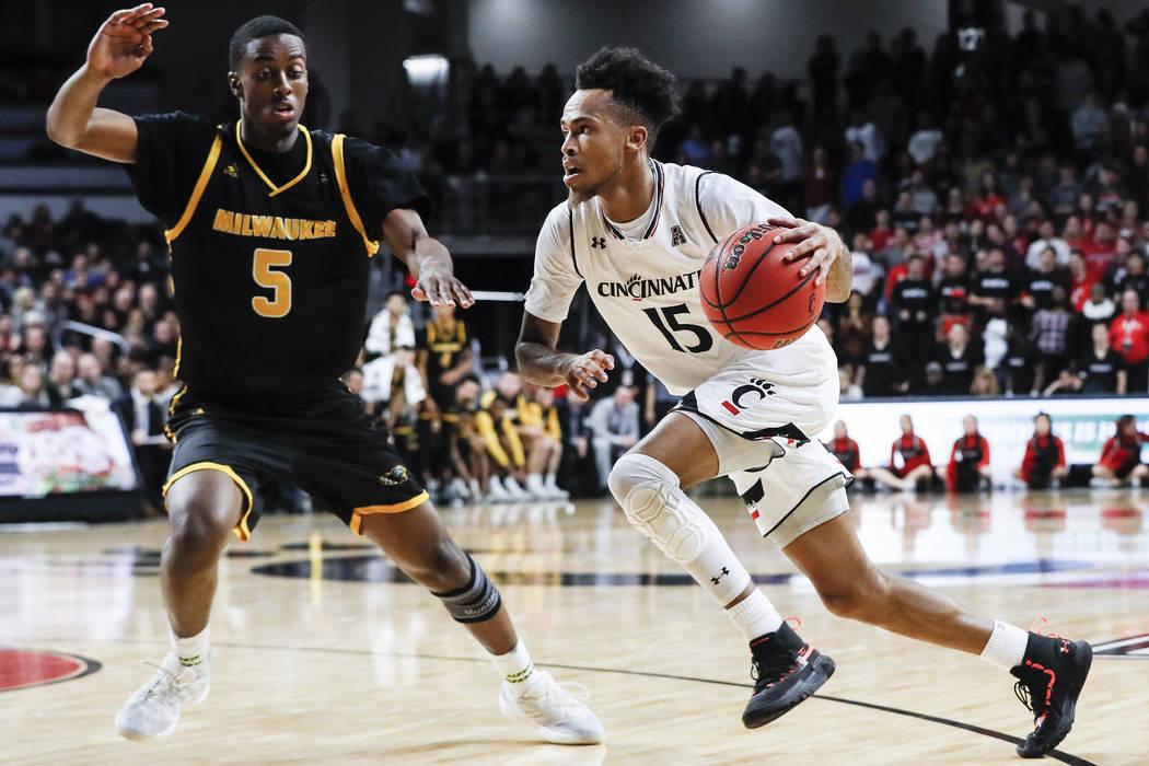 Cane Broome (15) de Cincinnati conduce como Carson Warren-Newsome de Milwaukee defiende durante la segunda mitad de un partido de baloncesto universitario de la NCAA el viernes 16 de noviembre de ...
