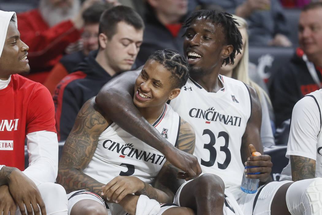Justin Jenifer de Cincinnati, centro izquierda, y Nysier Brooks (33) celebran en el banco durante la segunda mitad de un partido de baloncesto universitario de la NCAA contra Western Michigan, el ...