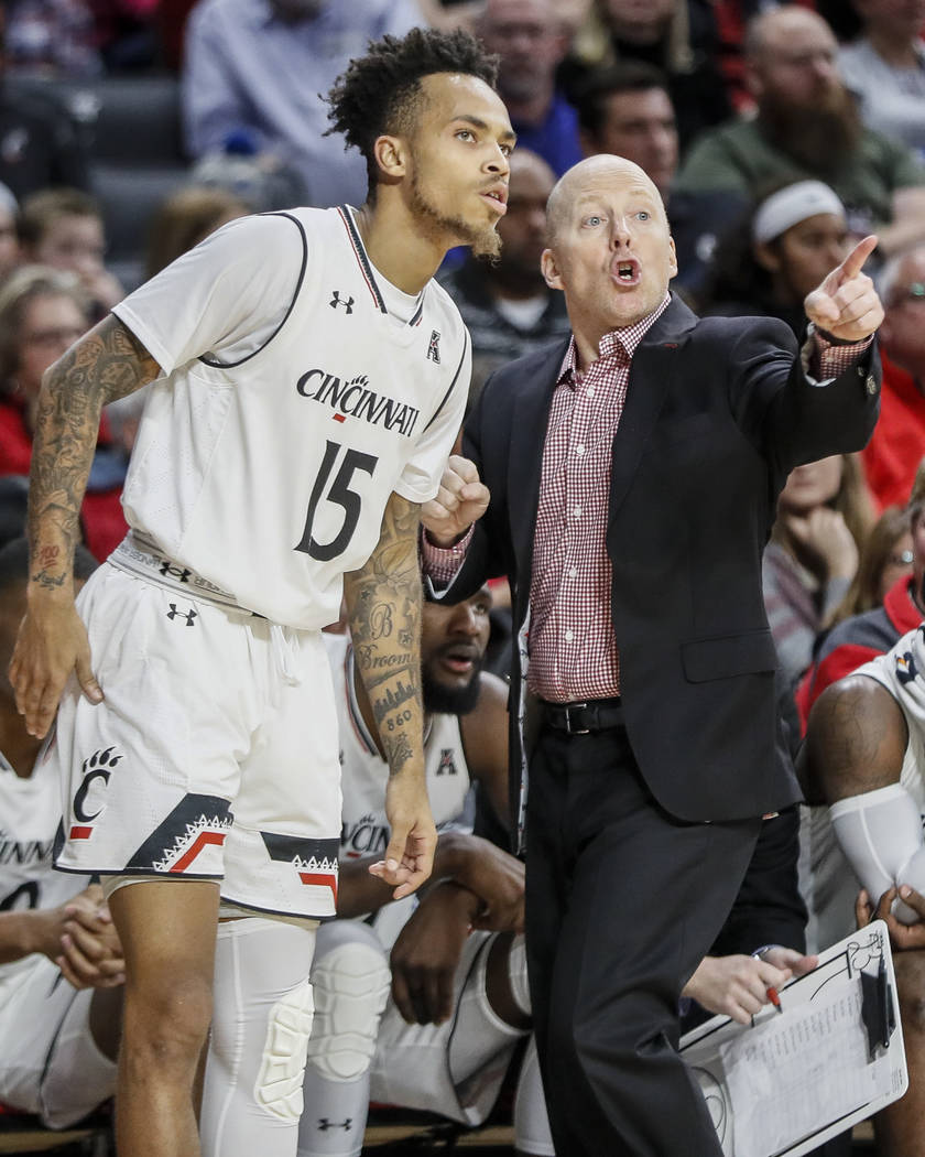 Cincinnati's head coach Mick Cronin, right, speaks with Cane Broome (15) in the second half of an NCAA college basketball game against Milwaukee, Friday, Nov. 16, 2018, in Cincinnati. (AP Photo/Jo ...