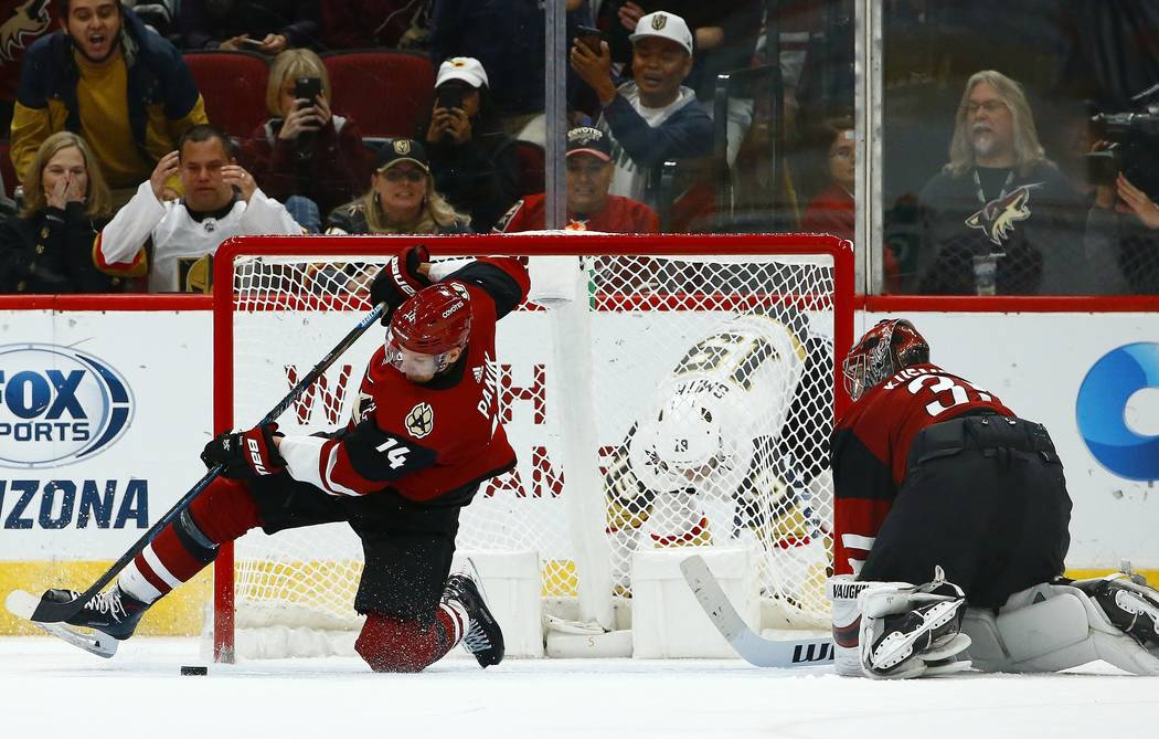 Arizona Coyotes right wing Richard Panik (14) makes a save for Coyotes goaltender Darcy Kuemper, right, on a shot from Vegas Golden Knights right wing Reilly Smith (19) during overtime of an NHL h ...