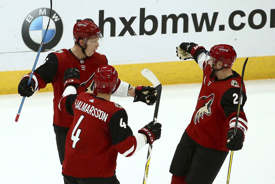 Arizona Coyotes center Derek Stepan (21) celebrates his goal against the Vegas Golden Knights with Coyotes defenseman Niklas Hjalmarsson (4) and defenseman Jakob Chychrun, left, during the first p ...