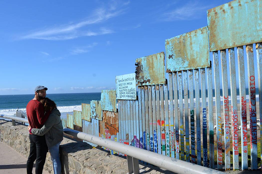 Dos jóvenes se abrazan frente a un letrero que dice: Ningún obstáculo nos puede impedir alcanzar nuestros sueños; somos mexicanos, somos imparables. Domingo 25 de noviembre de 2018, en Tijuana ...