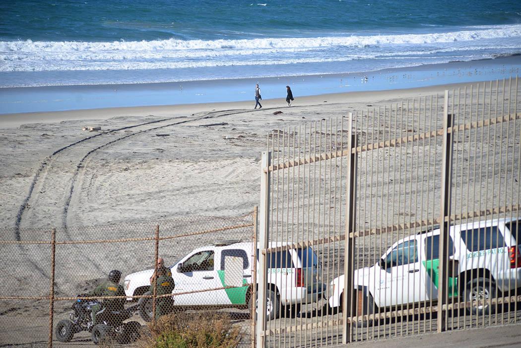 Dos turistas caminan en la playa, mientras la guardia fronteriza observa con atención los movimientos de algunos migrantes. Domingo 25 de noviembre de 2018, en Tijuana, Baja California Norte. Fot ...