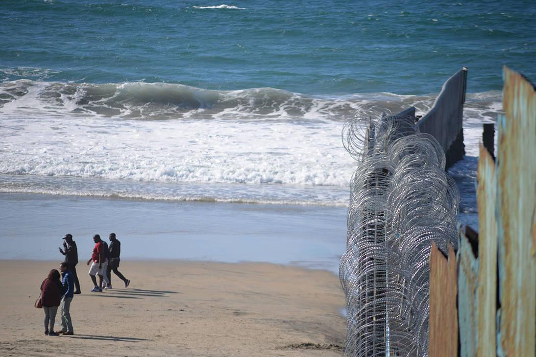 Las olas del océano Pacífico cortan la barda metálica que divide a México y Los Estados Unidos. Domingo 25 de noviembre de 2018, en Tijuana, Baja California Norte. Foto Frank Alejandre / El Ti ...
