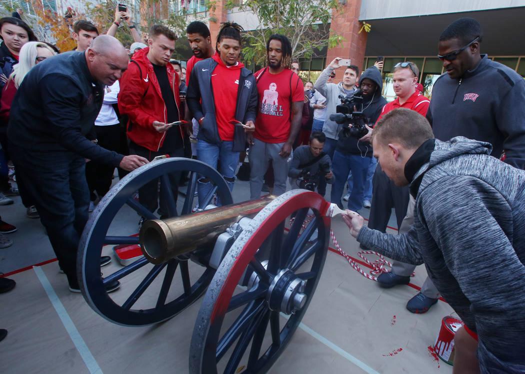 Los estudiantes y oficiales de la UNLV observan cómo los jugadores de fútbol de los Rebels, incluido el pateador Evan Pantels, a la derecha, y el entrenador en jefe, Tony Sánchez, a la izquierd ...
