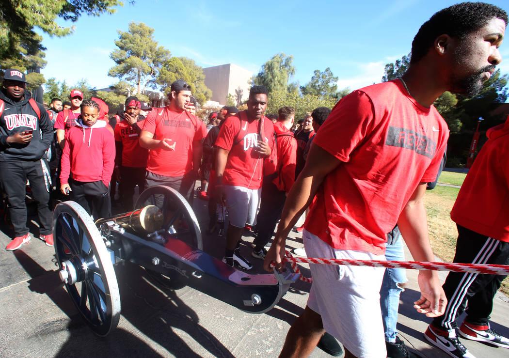Los jugadores de fútbol de la UNLV, incluido el mariscal de campo, Armani Rogers, al frente, sacan el cañón de Fremont para pintarlo de rojo fuera de la Unión de Estudiantes en la UNLV el lune ...