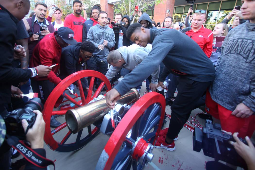 Estudiantes y oficiales de la UNLV observan cómo los jugadores de fútbol de los Rebels, incluido el linebacker Javin White, a la derecha, pintan de rojo el cañón de Fremont fuera de la Unión ...