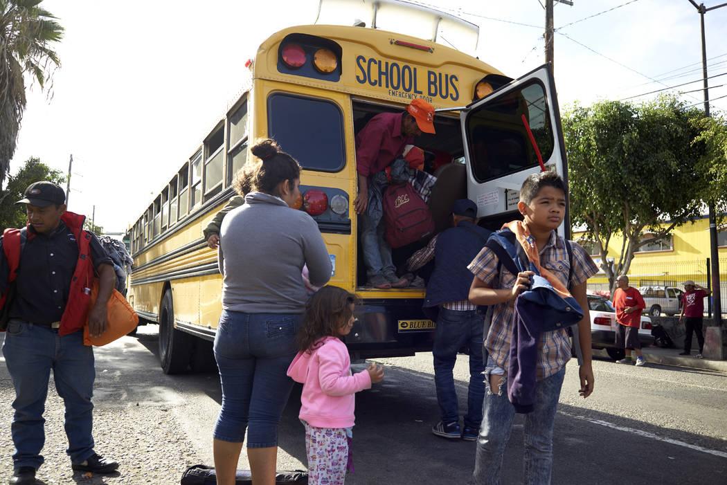 Los migrantes centroamericanos llegan en un autobús escolar a un refugio que ofrece desayuno en Tijuana, México, el jueves 15 de noviembre de 2018. Los miembros de una caravana de migrantes come ...