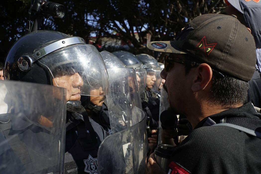 La policía se pone en guardia para proteger un refugio para migrantes mientras los manifestantes protestan por la presencia de miles de migrantes centroamericanos en Tijuana, México, el domingo ...