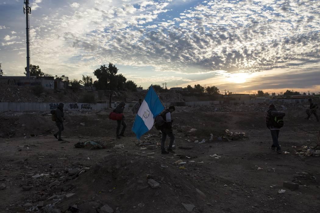 Un hombre que viaja con una caravana de migrantes centroamericanos lleva una bandera guatemalteca al amanecer cuando el grupo sale de Mexicali hacia Tijuana, México, el martes 20 de noviembre de ...