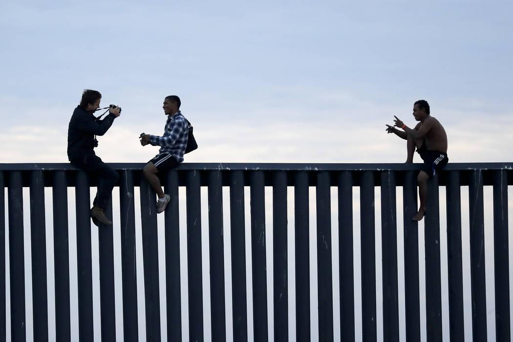 Dos hombres hondureños se hacen pasar por un fotógrafo que, a la izquierda, se toman una foto después de que el grupo subió el muro fronterizo que separa a Tijuana, México y San Diego, antes ...