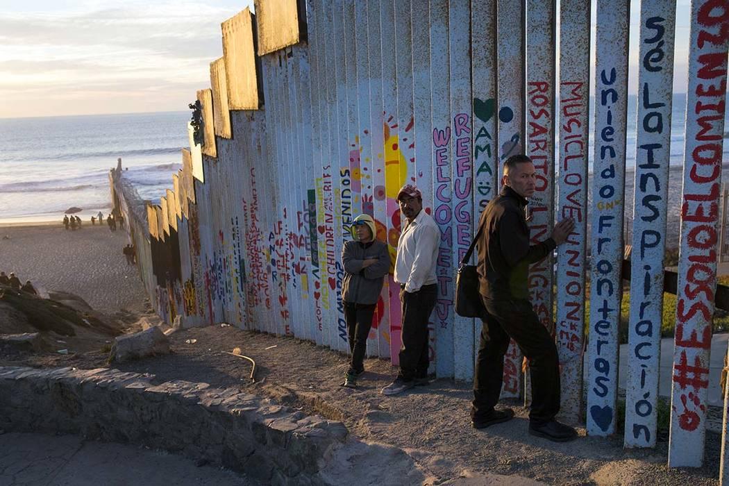 La gente se reúne en el lado mexicano de la estructura fronteriza que separa a México de los EE.UU., en el Océano Pacífico, Tijuana, México, viernes 16 de noviembre de 2018. Mientras miles de ...