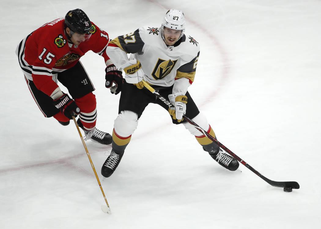 El defensa de los Golden Knights de Las Vegas, Shea Theodore (27), hace un pase del centro Artem Anisimov (15) de los Chicago Blackhawks durante el segundo período de un juego de hockey de la NHL ...
