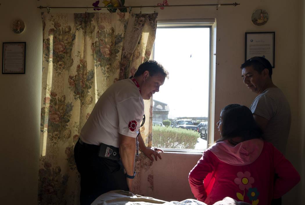 Scott Thompson, inspector de bomberos de Las Vegas Fire and Rescue, instruye a una niña y a su padre sobre los pasos a seguir en caso de incendio en un complejo de apartamentos en el Valle Centra ...