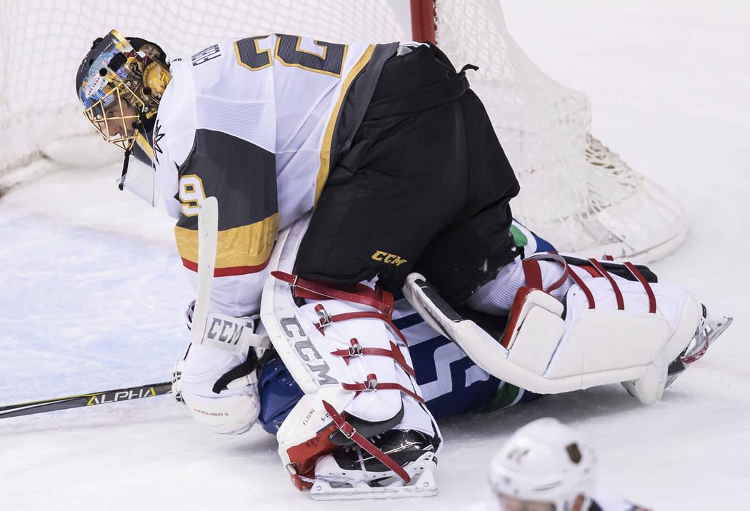 Tim Schaller, de Vancouver Canucks, en la parte inferior, se desliza debajo del portero Marc-André Fleury de los Golden Knights de Las Vegas durante el segundo período de un juego de hockey de l ...