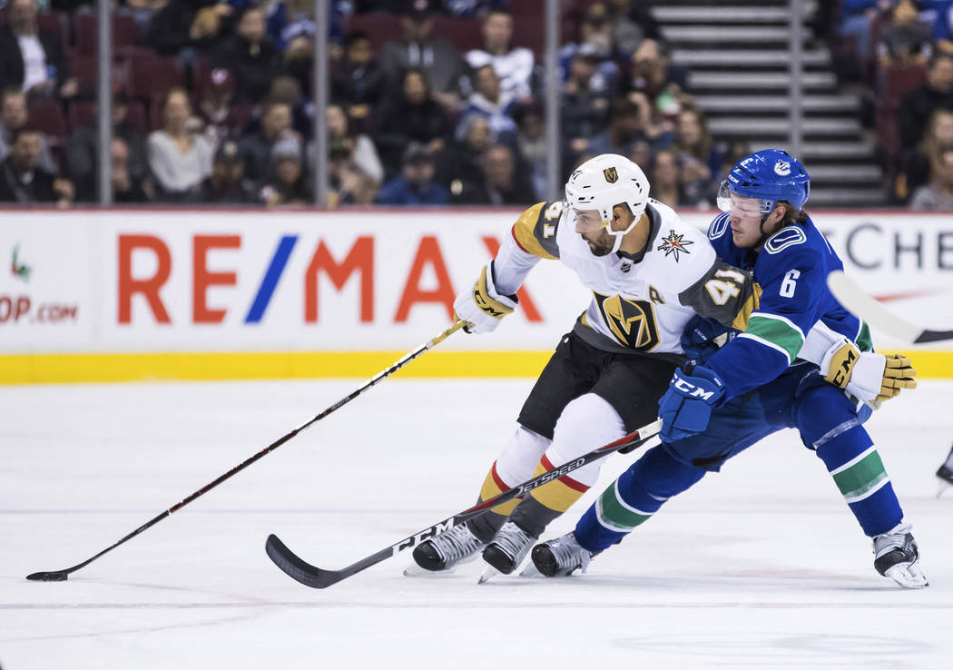 Pierre-Edouard Bellemare de Vegas Golden Knights (41) trata de contener a Brock Boeser (6) de los Vancouver Canucks mientras patina con el puck durante el primer período de un juego de hockey de ...