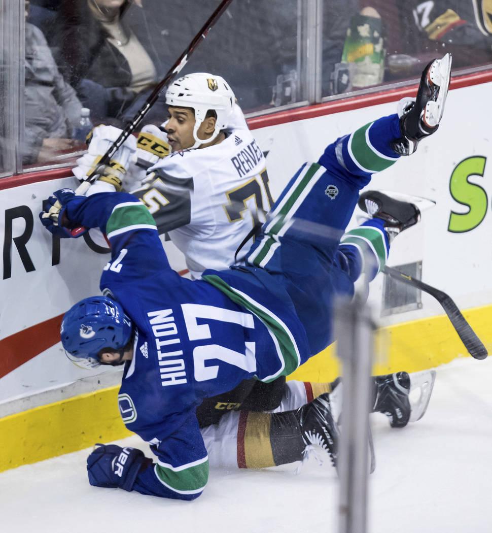 Ben Hutton (27) de los Vancouver Canucks y Ryan Reaves (75) de los Golden Knights de Las Vegas se enfrentan durante el segundo período de un juego de hockey de la NHL el jueves 29 de noviembre de ...