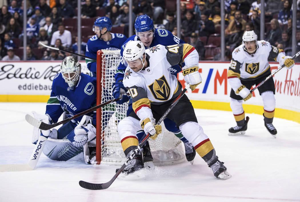 Ryan Carpenter (40) de los Golden Knights de Las Vegas patina alrededor de la red con el disco detrás del portero de los Vancouver Canucks Jacob Markstrom, izquierda, de Suecia, mientras Adam Gau ...