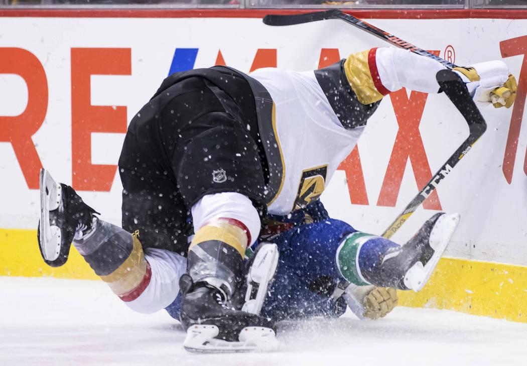 William Carrier de los Vegas, los Golden Knights, y Alex Biega, de los Vancouver Canucks, caen al hielo luego de colisionar durante el primer período de un juego de hockey de la NHL el jueves 29 ...