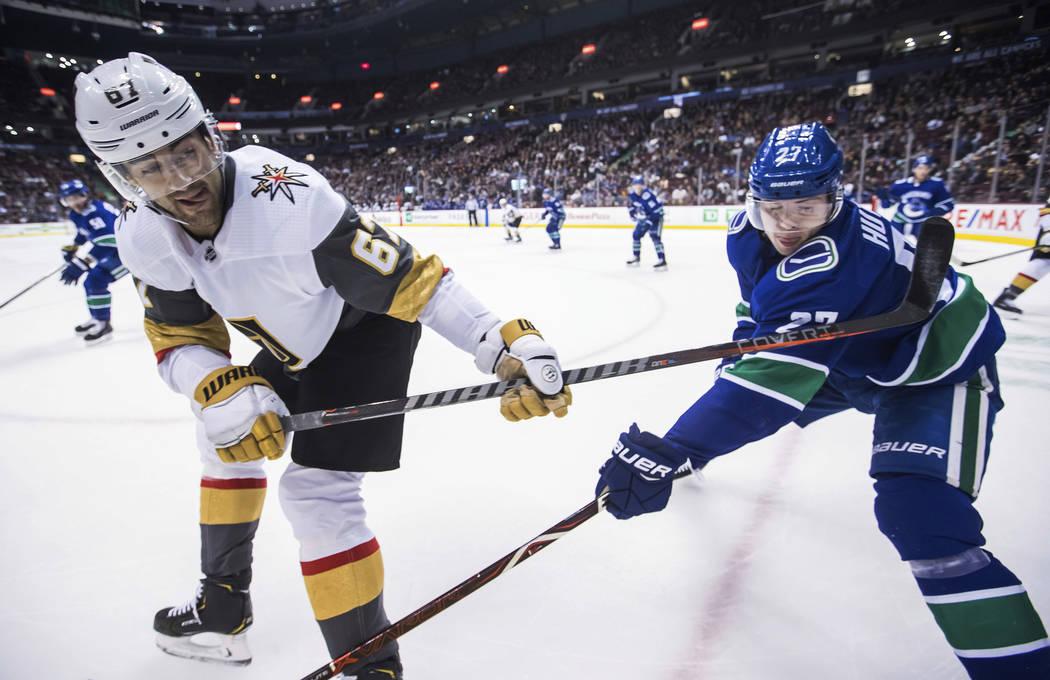 Max Pacioretty de los Golden Knights de Las Vegas, a la izquierda, pasa el disco pasando por Ben Hutton de los Vancouver Canucks durante el primer período de un juego de hockey de la NHL el 29 de ...