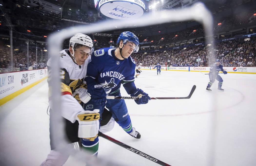 Tomas Nosek, de la República Checa, a la izquierda de los Vegas Golden Knights, es controlado por Ben Hutton de Vancouver Canucks durante el primer período de un juego de hockey de la NHL el jue ...