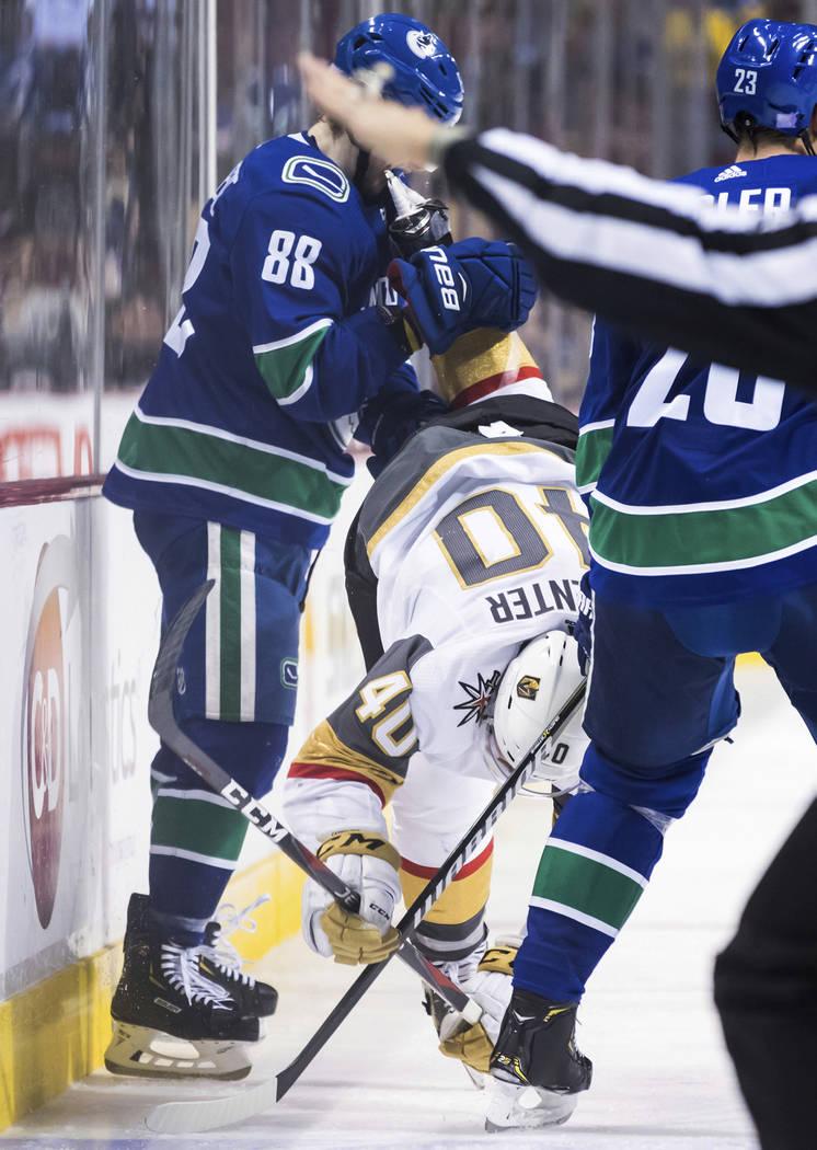 Adam Gaudette (88) de Vancouver Canucks recibe un golpe en la cara con el patín de Ryan Carpenter de los Vegas Golden Knights durante el tercer período de un juego de hockey de la NHL el jueves ...