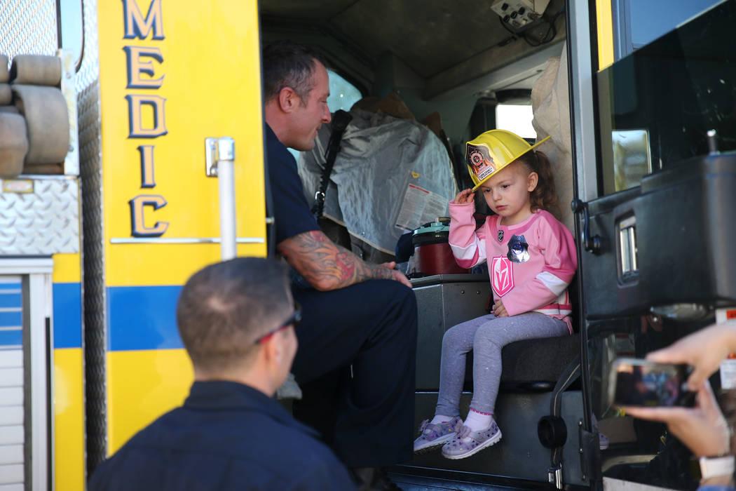 Scarlett Mize, de 3 años, se sienta dentro de un camión de bomberos con el bombero del Departamento de Bomberos del Condado de Clark, Jonathan McBreen, durante una visita de concientización sob ...