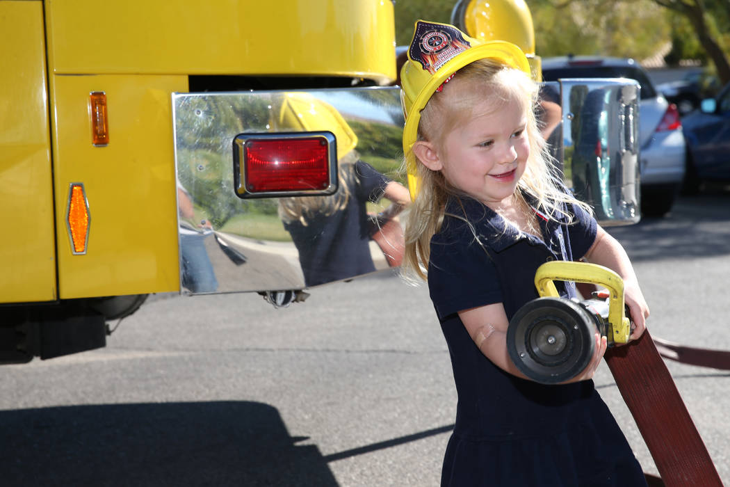 Stella Peck, de 4 años, sostiene una manguera de agua de un camión de bomberos durante una visita de concienciación sobre incendios realizada por el Departamento de Bomberos del Condado de Clar ...