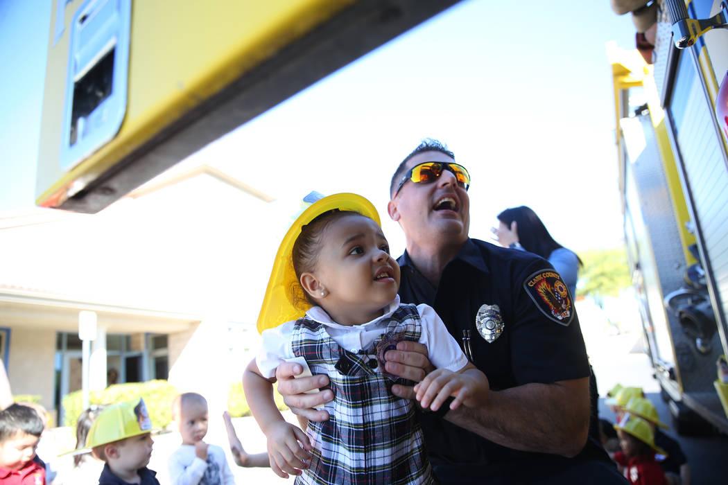El bombero del Departamento de Bomberos del Condado de Clark, Adam Smith, lleva a Giovanna McMurry, de 3 años, a un camión de bomberos durante una visita de concientización sobre incendios en M ...