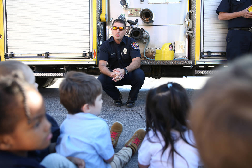 El bombero del Departamento de Bomberos del Condado de Clark, Adam Smith, habla a los niños durante una visita de concientización sobre incendios en Merryhill Preschool, 5055 S. Durango Dr., en ...