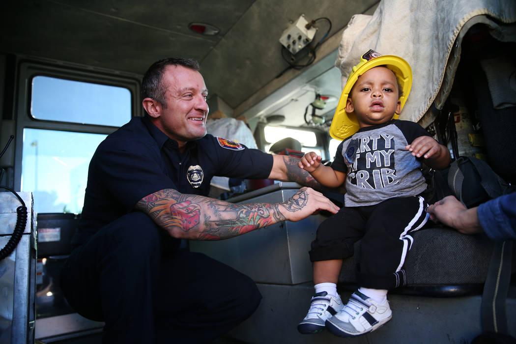 El bombero del Departamento de Bomberos del Condado de Clark, Jonathan McBreen, a la izquierda, muestra a Avery Duncan, 1, dentro de un camión de bomberos durante una visita de concientización s ...
