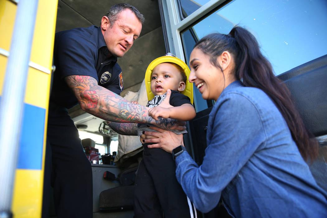 El bombero del Departamento de Bomberos del condado de Clark, Jonathan McBreen, a la izquierda, después de mostrar a Avery Duncan, 1, dentro de un camión de bomberos con la co-líder infantil Fe ...