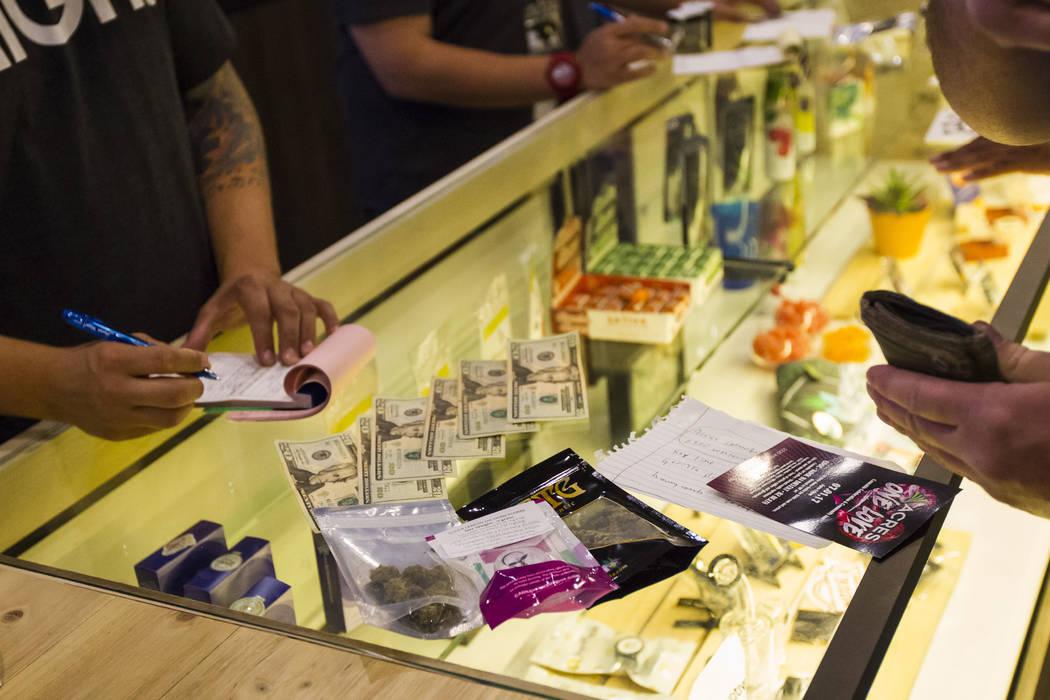 El residente de Henderson, Ethan, a la derecha, compra productos de marihuana durante el primer día de ventas recreativas en Acres Cannabis en Las Vegas el sábado 1 de julio de 2017. Chase Steve ...