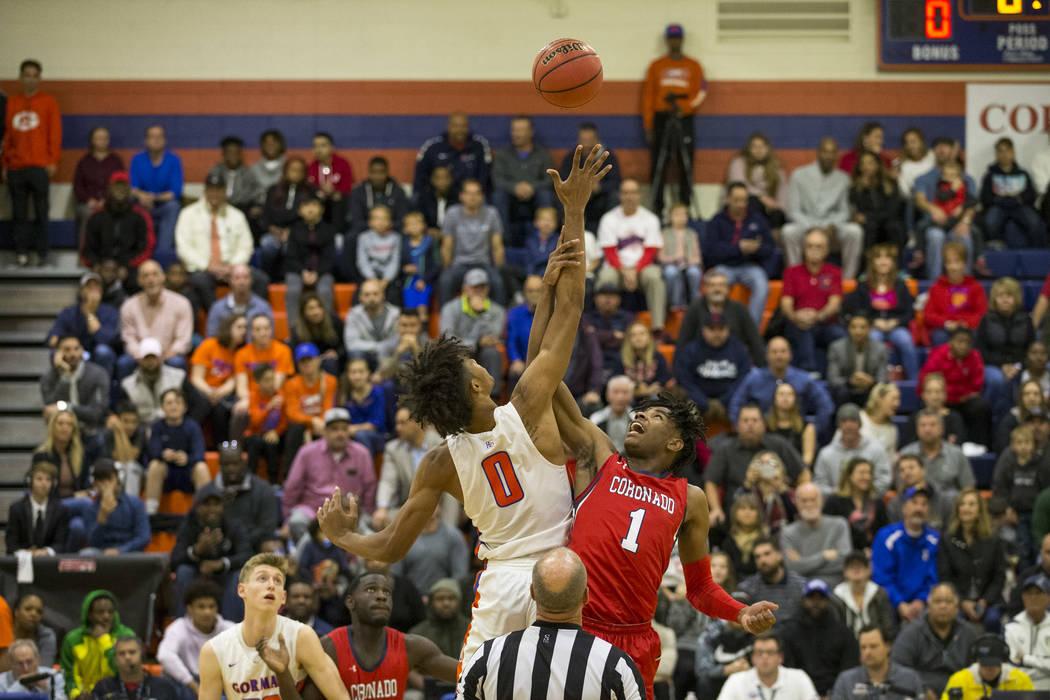 Isaiah Cottrell (0) de Bishop Gorman y Jaden Hardy (1) de Coronado dan un salto durante la primera mitad de un partido de baloncesto en la escuela secundaria Bishop Gorman en Las Vegas el jueves, ...
