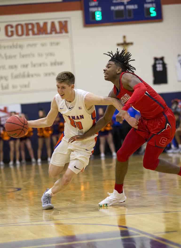 Noah Taitz (20) de Bishop Gorman conduce el balón contra Jaden Hardy (1) de Coronado durante la primera mitad de un juego de baloncesto en la escuela secundaria Bishop Gorman en Las Vegas el juev ...