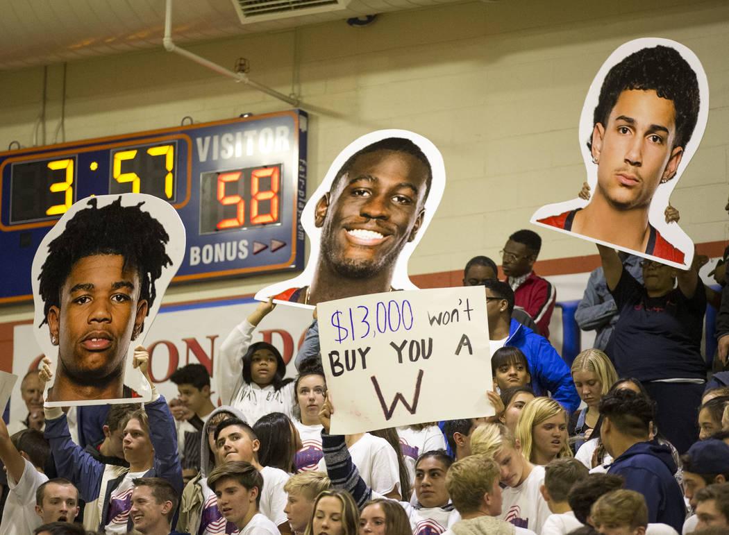 Los fans de Coronado sostienen carteles durante la segunda mitad de un juego de baloncesto del equipo universitario contra Bishop Gorman en la Preparatoria Bishop Gorman en Las Vegas el jueves 29 ...