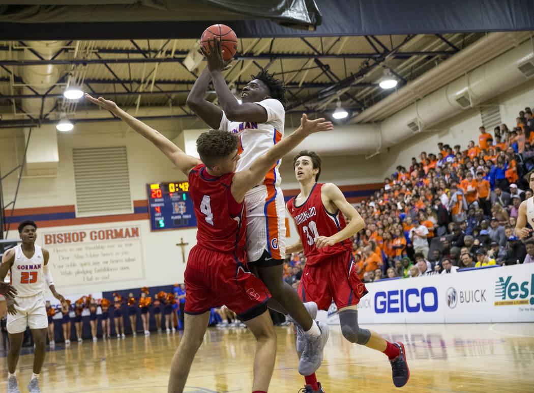 Will McClendon (1) de Bishop Gorman lanza sobre Nick Walters (4) de Coronado durante la primer mitad de un partido de baloncesto del equipo universitario Bishop Gorman High School en Las Vegas el ...