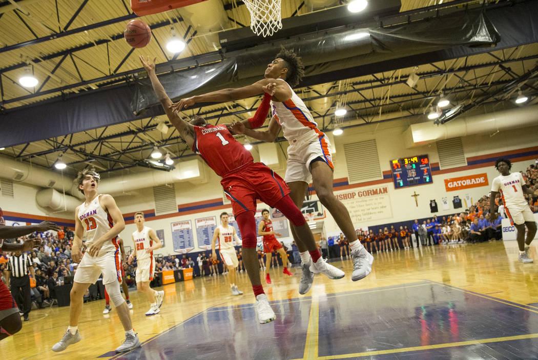 Jaden Hardy (1) de Coronado se ve bloqueado por Isaiah Cottrell (0) de Bishop Gorman durante la segunda mitad de un juego de baloncesto en la escuela secundaria Bishop Gorman en Las Vegas el jueve ...