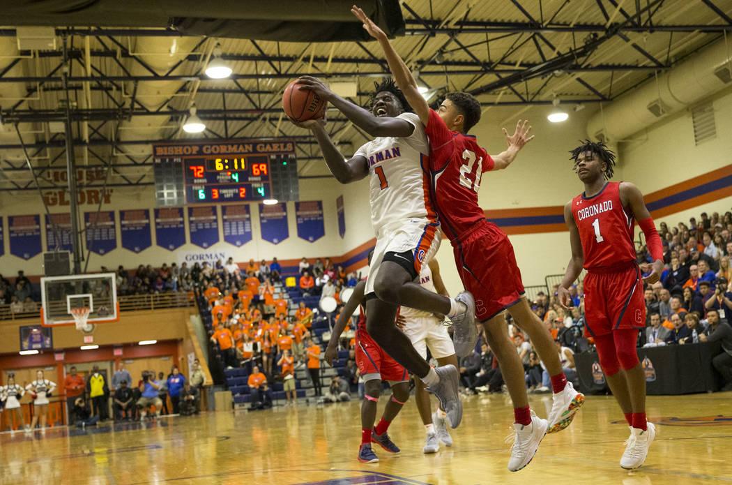 Will McClendon (1), de Bishop Gorman, intenta un disparo contra Max Howard (21) de Coronado durante la segunda mitad de un juego de baloncesto en la Preparatoria Bishop Gorman en Las Vegas el juev ...