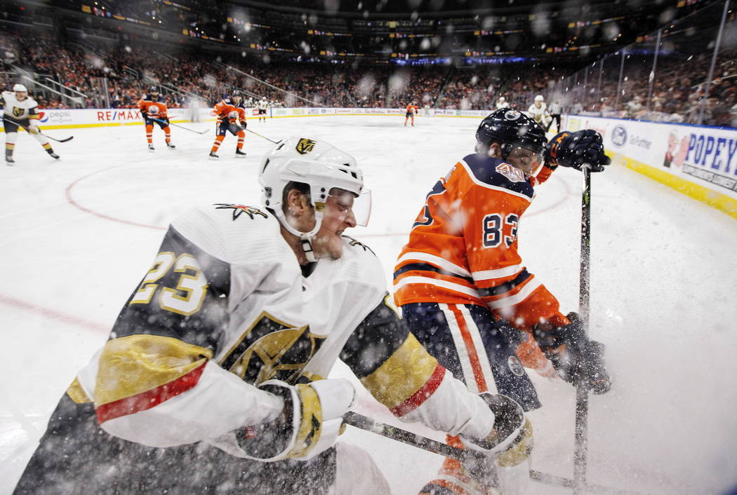Daniel Carr (23) de los Golden Knights de Vegas y Matthew Benning (83) de los Edmonton Oilers luchan por el disco durante el tercer período de un juego de hockey de la NHL el sábado 1 de diciemb ...