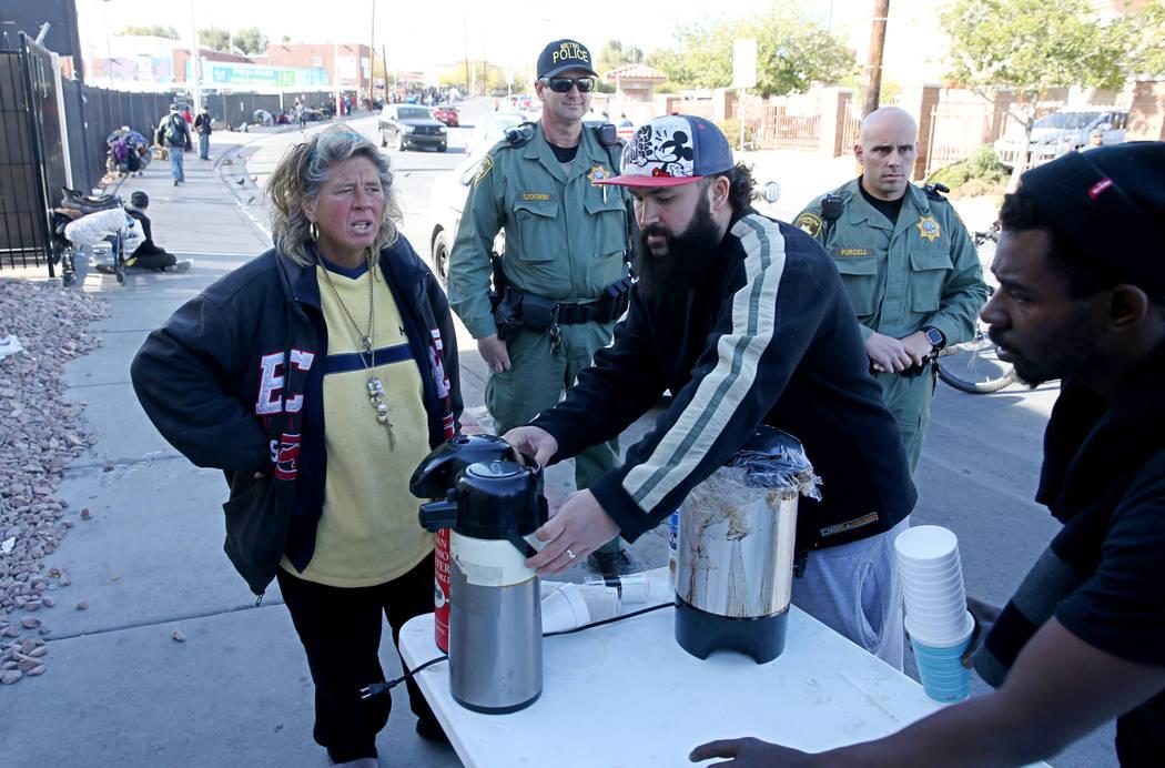 La policía de Las Vegas observa a Joey Lankowski, centro, limpiar el área donde estaba distribuyendo comida en Foremaster Lane, cerca de Las Vegas Boulevard, el miércoles 28 de noviembre de 201 ...