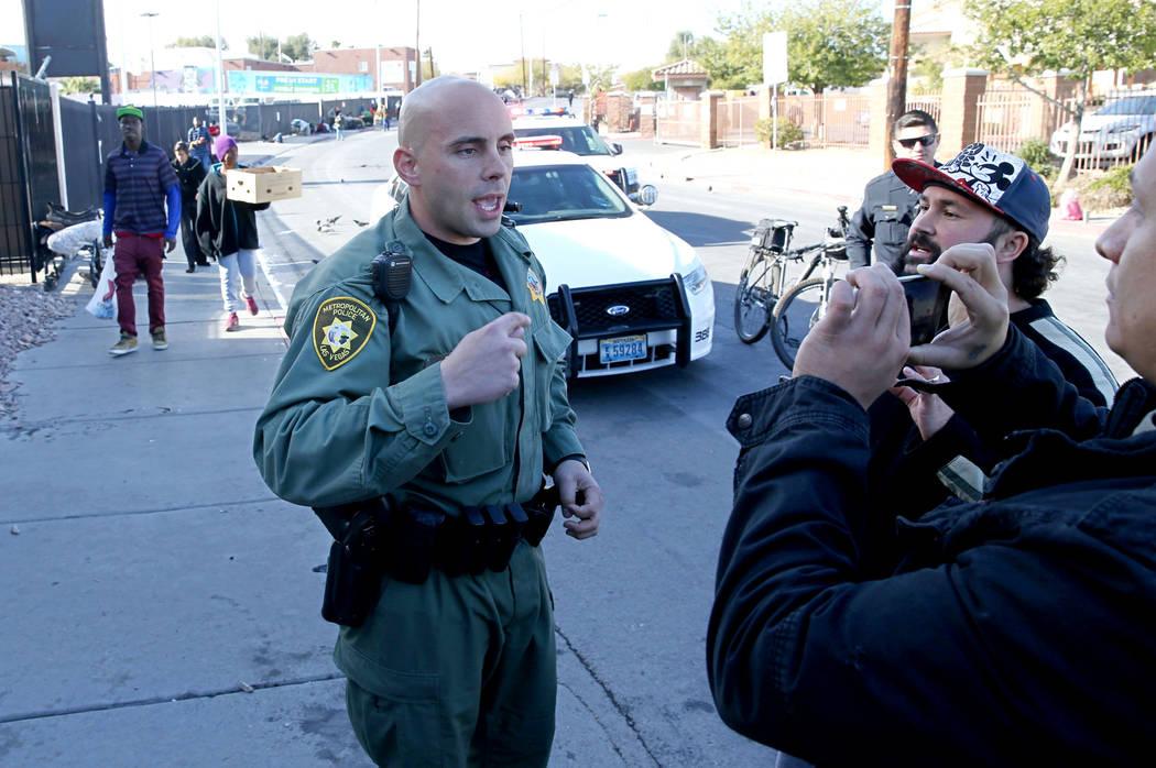 Un oficial de la policía de Las Vegas discute con Joey Lankowski, segundo a la derecha, y Joshua Martinezm donde Lankowski estaba distribuyendo comida en Foremaster Lane, cerca de Las Vegas Boule ...