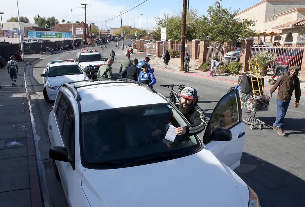 Joey Lankowski toma una multa de su parabrisas donde estaba distribuyendo comida en Foremaster Lane, cerca de Las Vegas Boulevard, el miércoles 28 de noviembre de 2018. Lankowski fue penalizado p ...
