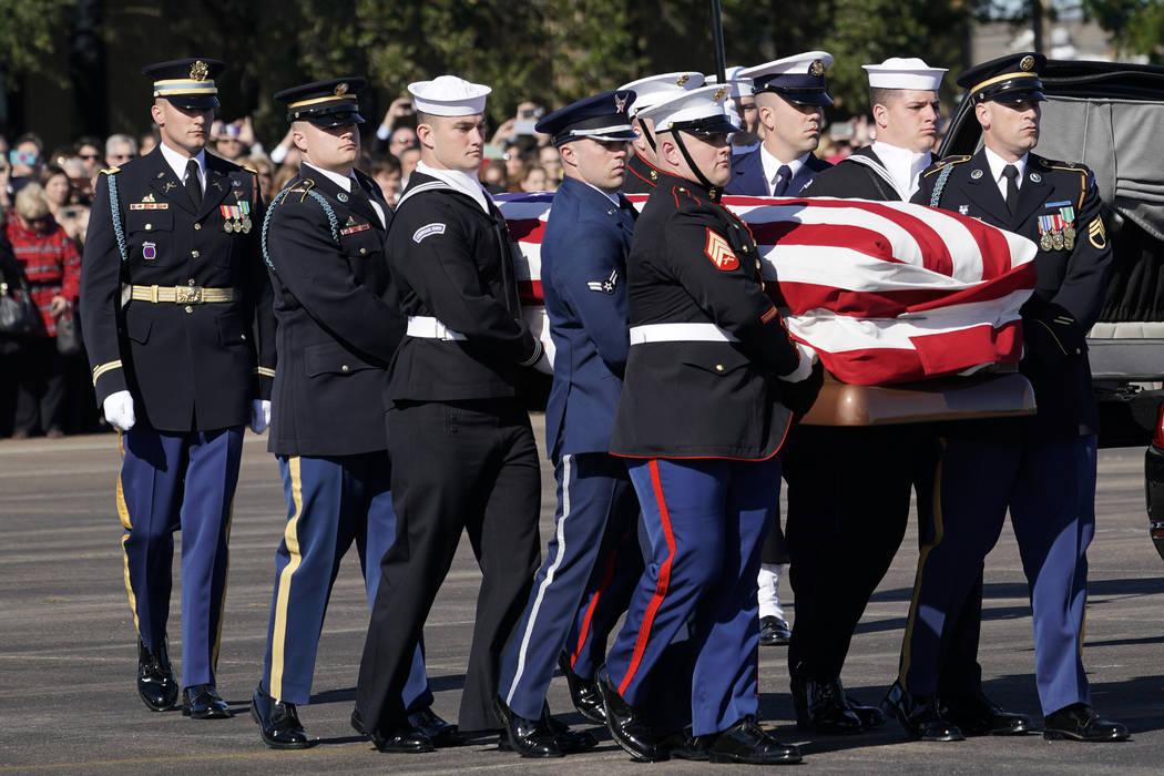 El ataúd abanderado del ex presidente George H.W. Bush es llevado por una guardia de honor militar de servicios conjuntos a la Misión Aérea Especial 41 en Ellington Field durante una ceremonia ...